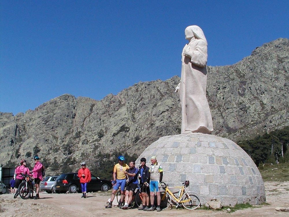 Cyclists pose by some Roman Catholic thingumibob at Col de Vergio
